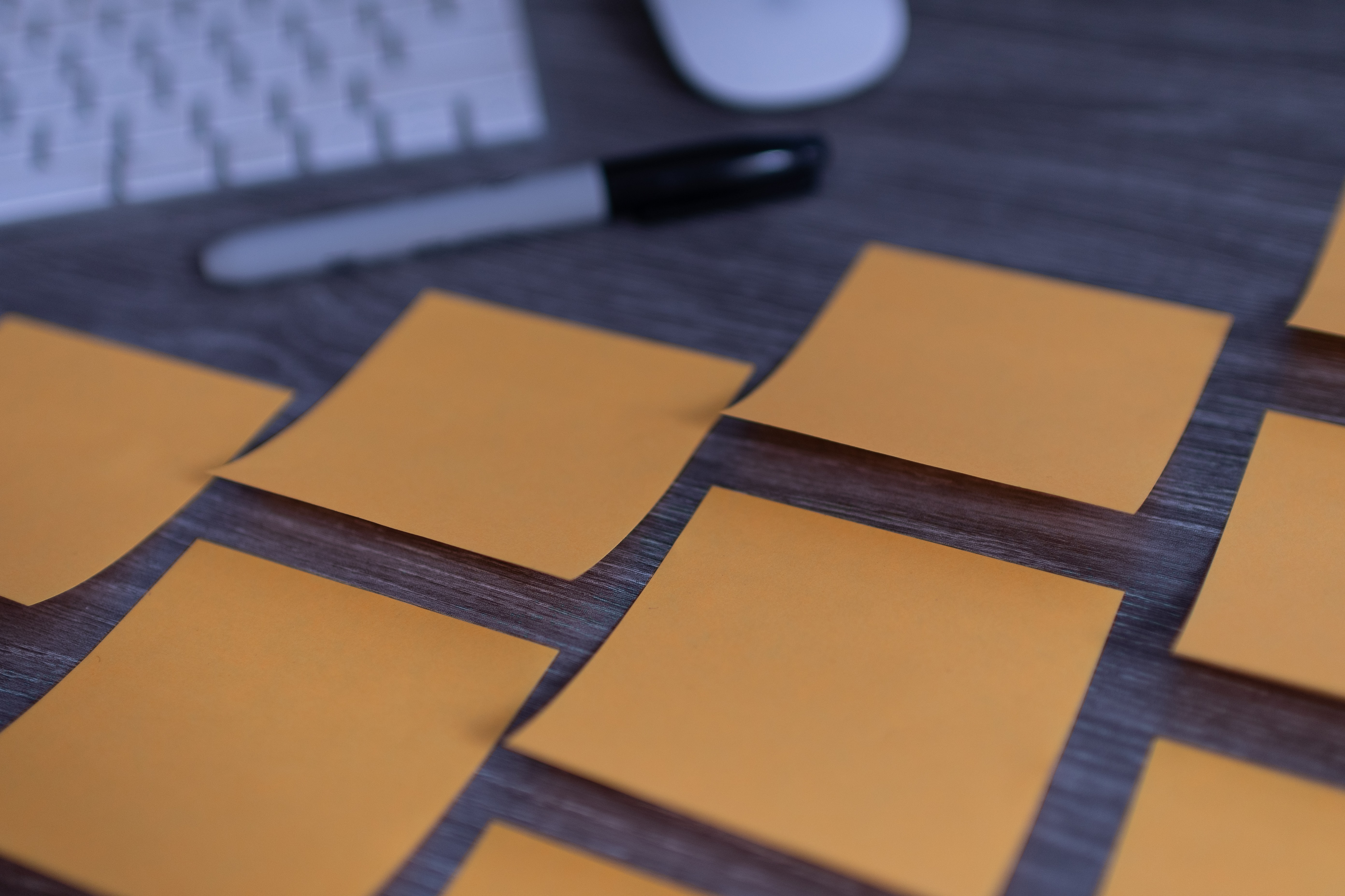 Orange post-it notes laid out next to a keyboard and sharpie