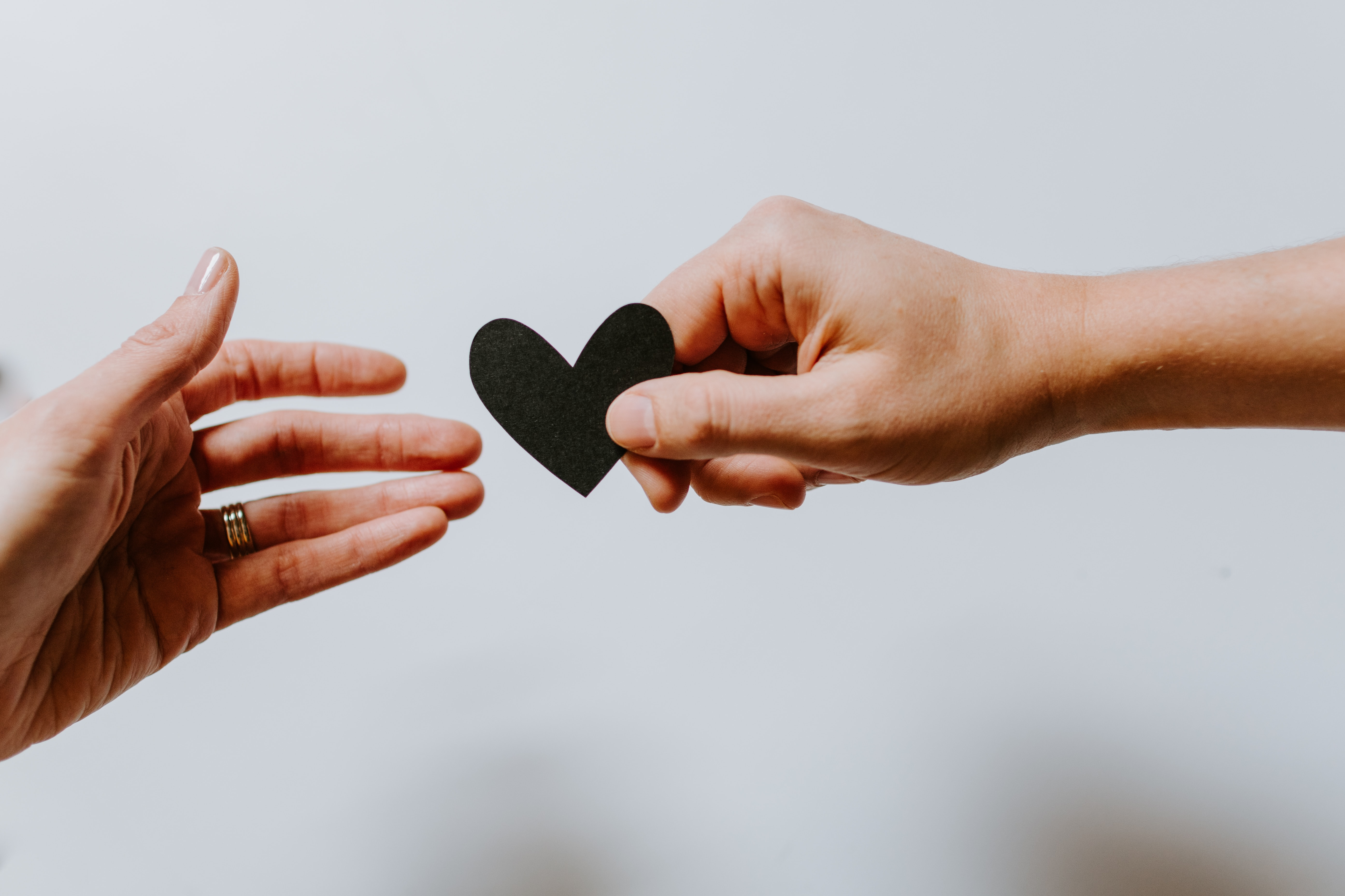 Two hands passing a small black paper heart