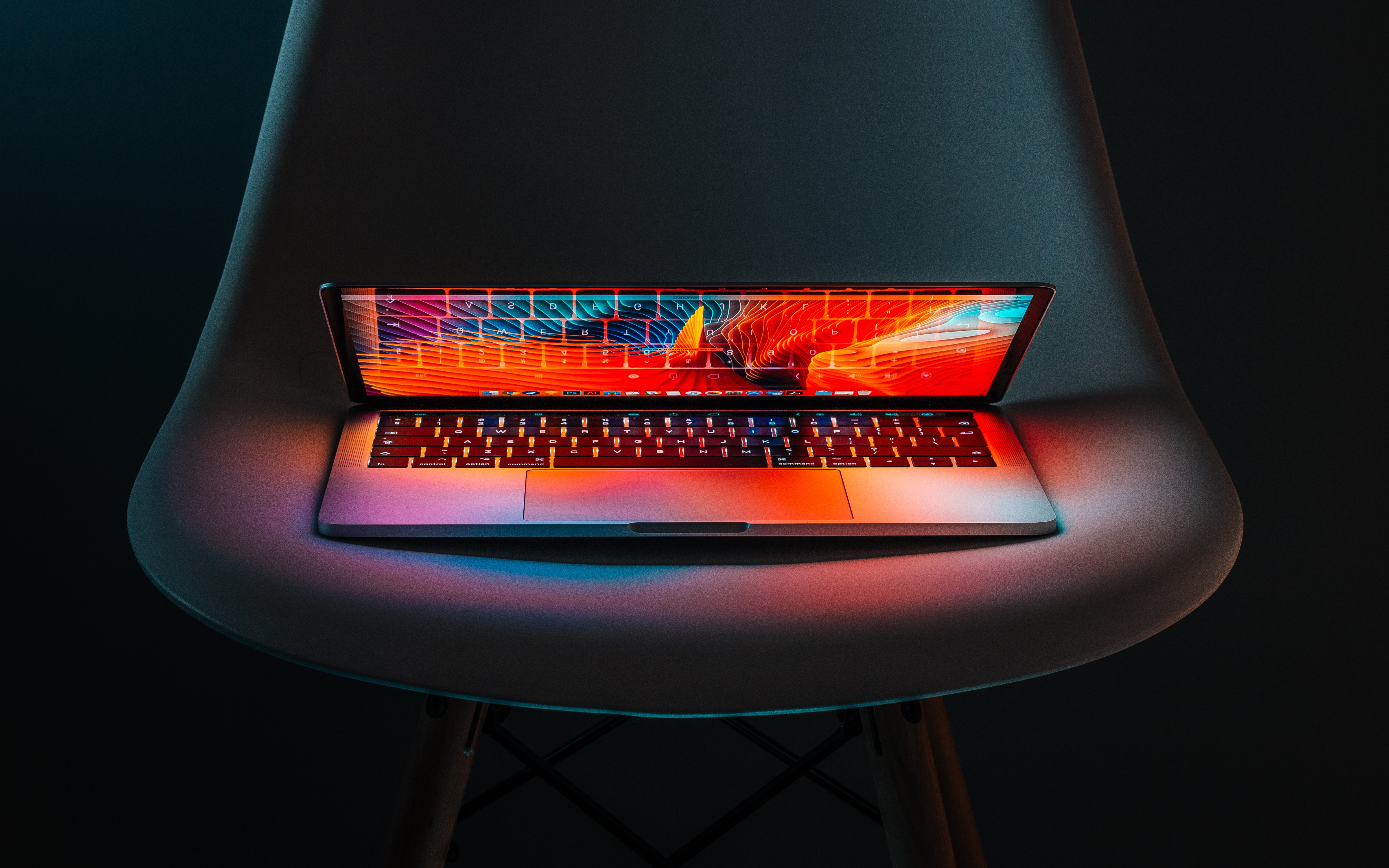 A laptop sitting on a chair partially open, glowing, in the dark