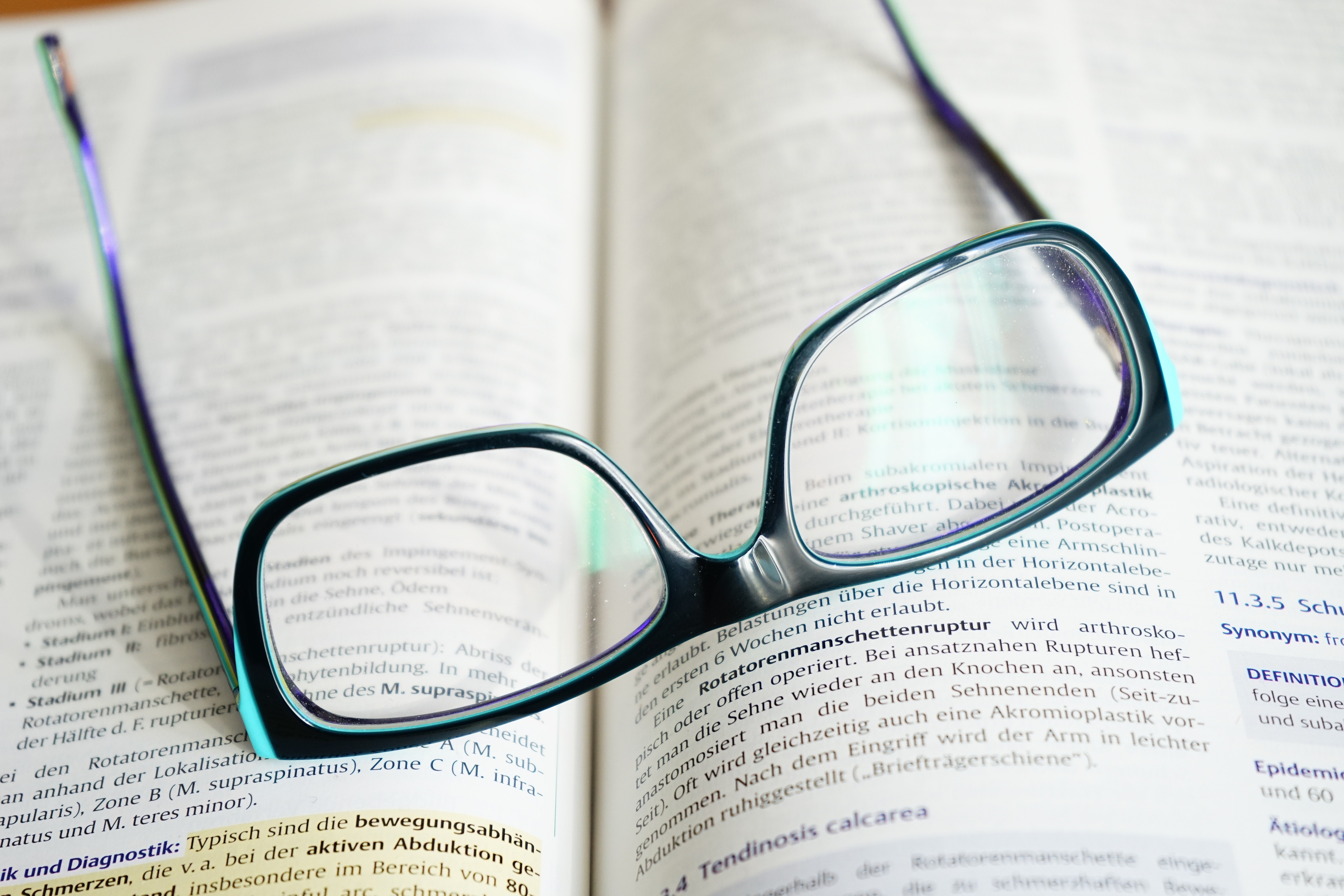 Close up of a pair of glasses lying on top of a textbook